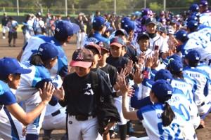 試合後、両チームの選手らからタッチを交わした小学生ら=28日、名瀬運動公園市民球場