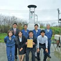 特許登録を喜ぶトマス技研の社員と、福富社長(後列右から2人目)=13日、沖縄・うるま市