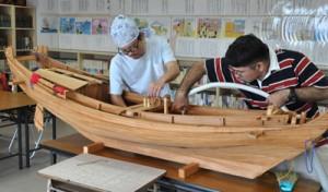 報恩丸の模型を補修する越来勇喜さん(左)=23日、和泊町の西郷南洲記念館