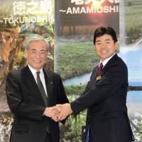 会見で握手を交わすJALの本田執行役員(右)と朝山市長=19日、奄美市名瀬