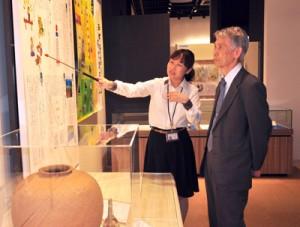 展示資料について説明を受ける拓殖大学の福田勝幸理事長(右)=24日、龍郷町りゅうゆう館
