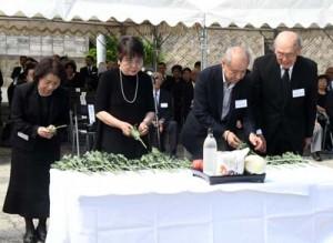 祭壇に献花して犠牲者のみ霊を慰める遺族ら=20日、徳之島町亀徳
