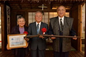 火縄銃を寄贈した(写真左から)若志ヤヨイさんと夫の茂義さん、竹田町長=2日、龍郷町