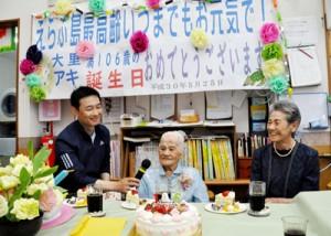 家族や施設職員、仲間に見守られて106歳の誕生日を迎えた大里アキさん(中央)=25日、和泊町国頭