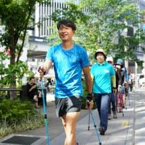 ポール(ノルディック)ウオーキング講習会で、参加者と共に銀座の街を歩く荻原健司さん=12日 東京都中央区