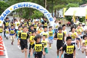 一斉にスタートを切った2キロコースの参加者ら=27日、大和村の村体育館前