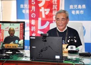 対戦する広島県三次市の増田市長と電話でエール交換する朝山市長=7日、奄美市役所