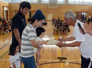 安田区長から賞状と祝い金を受け取る新生児と家族=5日、宇検村田検中体育館