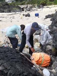 オカヤドカリの産卵場所を確保しようと漂着ごみを回収する参加者=13日、徳之島町金見崎海岸