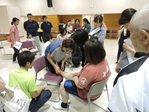 正しいテーピング方法を学ぶ参加者=22日、喜界町役場多目的ホール