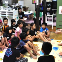 講師の林さん(右)と共に楽しく英語を学ぶ子どもたち=26日、和泊町伊延