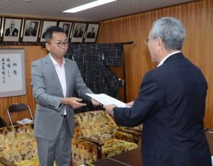 奄美大島への大学設立の可能性について意見具申する勝座長(左)=2日、奄美市役所