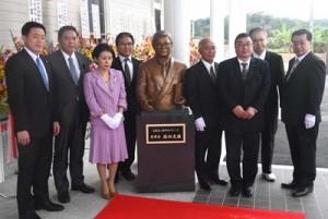 開館した徳田虎雄顕彰記念館(上)と徳田氏の銅像を囲み開館を祝う関係者=28日、徳之島町亀徳