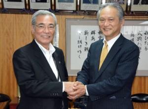 8月からの鹿児島―奄美大島便就航の抱負を語り、朝山市長(左)と握手を交わすスカイマークの市江社長=14日、奄美市役所