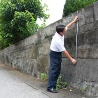 道路に面した学校の塀の高さを測る伊津部小学校の末吉校長=21日、奄美市名瀬