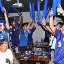 大迫選手のゴールに総立ちで喜ぶ沖永良部サッカー協会の会員ら=19日、和泊町