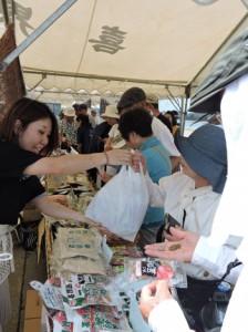約400人を乗せて寄港した「にっぽん丸」(上)。乗客でにぎわう特産品販売コーナー=6日、喜界町湾港