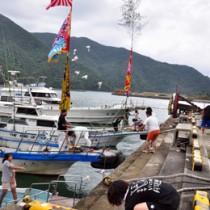 船上からの餅投げに歓声が上がった山間集落の浜下れ行事=3日、奄美市住用町の山間港