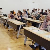 指体操の難しさに思わず笑みがこぼれる参加者=26日、龍郷町
