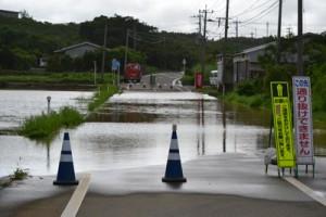 大雨で冠水し、通行止めとなった与論島内の県道=16日午後5時半ごろ、与論町那間