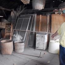喜界島から疎開した家族が住んでいたという畜舎の2階で当時の様子を語る松下さん=15日、伊佐市菱刈