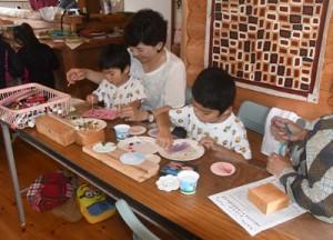 開校した「藝術楽校」でアボリジナルアートを制作する参加者ら=24日、天城町三京