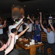 日本代表の勝利に万歳で喜びを爆発させる島のサポーターら=19日午後10時50分すぎ、奄美市名瀬のエリア13