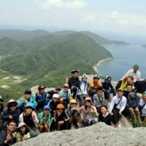 大山・ミヨチョン岳の絶景を背景に記念撮影する参加者=2日、瀬戸内町請島
