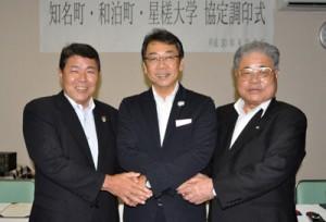 連携協定を結び、固く握手を交わす(左から)今井町長、井上学長、伊地知町長=9日、知名町