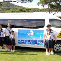 スクールバスを前に記念撮影する伊子茂小中の子どもたち=12日、瀬戸内町加計呂麻島の同校