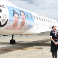 鈴木亮平さんと二階堂ふみさんが描かれたJACの特別塗装機=17日、霧島市の鹿児島空港