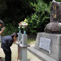 慰霊碑に手を合わせる栫静さん(右)=23日、瀬戸内町三浦