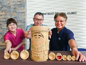西郷隆盛のオブジェと松尾院長(右)ら=9日、鹿児島市の松尾歯科医院
