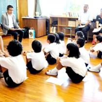 岩崎アナと森アナの朗読に聞き入る児童ら=6月29日、奄美市笠利町