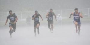 男子40代100メートル決勝。激しく降る雨とも戦いながらゴールへ向かう出場選手=21日、奄美市の名瀬運動公園陸上競技場