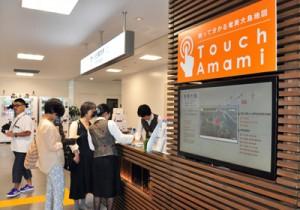 タッチパネル方式で島内情報を提供するモニター(奥は総合案内所)=9日、奄美市笠利町の奄美空港