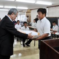 修了生2人に修了証書を手渡し、新たな研修生2人を紹介した修了・入所式=5日、奄美市役所