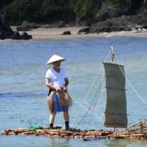 琉球列島間の交易や移住で使われた舟の検証で筏舟の進水実験をする日本工業大学特別研究員の基さん=22日、天城町の平土野漁港