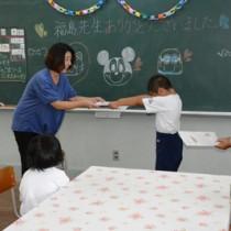 給食技師の福島さんにメッセージカードを渡す児童ら=19日、奄美市名瀬