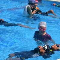 着衣水泳を体験する茶花小の児童=13日、与論町