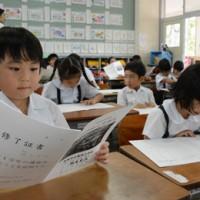 初めての通知表を見つめる小学1年生=20日、奄美市の名瀬小学校