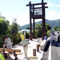 設備に焼酎と塩をまき安全祈願する関係者。後方が新設された見張り台=15日、宇検村芦検
