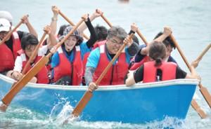 太鼓の音に合わせて懸命にかいをこぐ、くり舟競争の参加者=29日、知名町の知名漁港