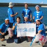 青いサンタの格好でボランティア清掃に汗を流した参加者=15日、知名町