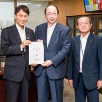 中川環境大臣(中央)に提案書を手渡す柴立会長(右)と三反園知事(左)=3日、環境省