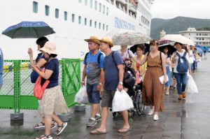 雨の中、船に乗るため列をつくる乗客