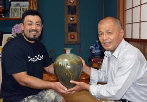 山神さん(左)から古希祝いの薩摩焼を受け取る稲田さん=16日、奄美市名瀬