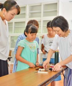 増田さん(写真右)から紬の髪飾り作りを教わった参加者たち=28日、奄美市名瀬浦上町の奄美市産業支援センター