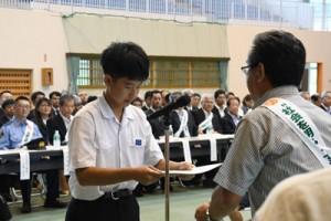 一日保護観察所長の委嘱状を受け取る中村さん(左)=3日、奄美市住用町