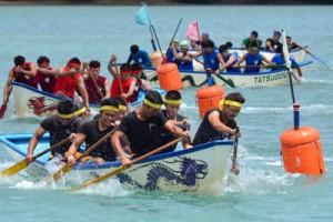 力強いかいさばきで折り返しのブイを回る各出場艇の選手=22日、龍郷町の玉里漁港